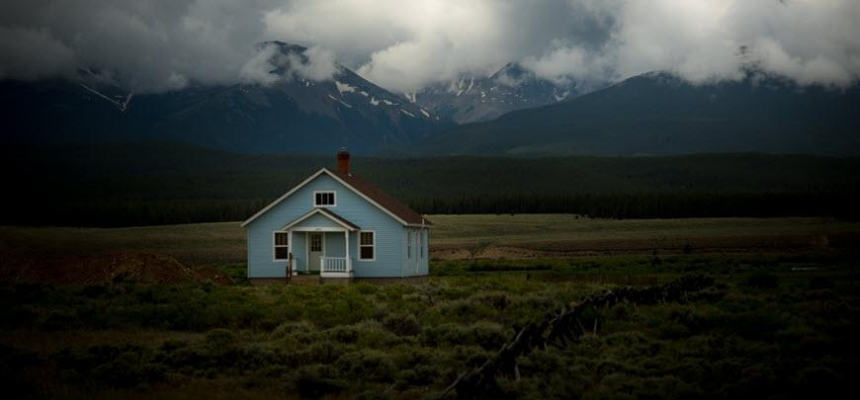 Colorado home in front of cloudy mountains