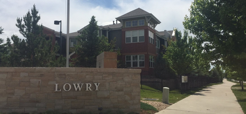 Brick wall with Lowry sign in front of building