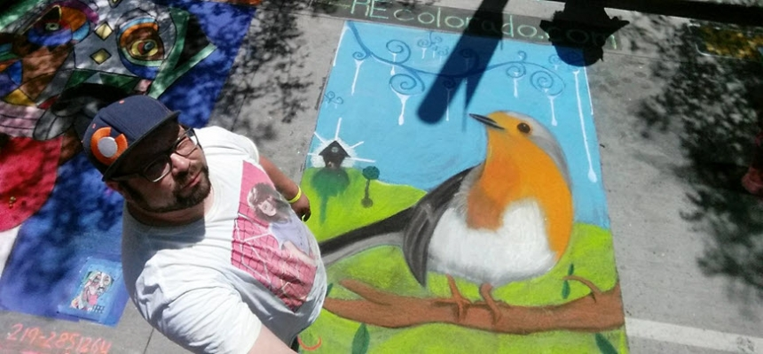 Chalk Artist Nathan Reker standing next to his complete drawing of an orange bird at the Denver Chalk Art Festival.