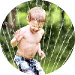 child playing sprinkler in yard