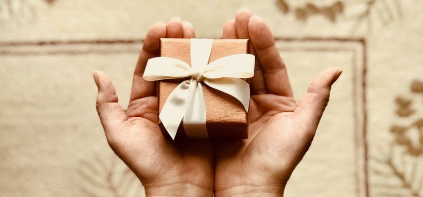 hands holding gift brown package holiday giving