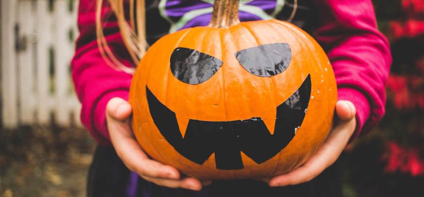 halloween costume girl holding pumpkin