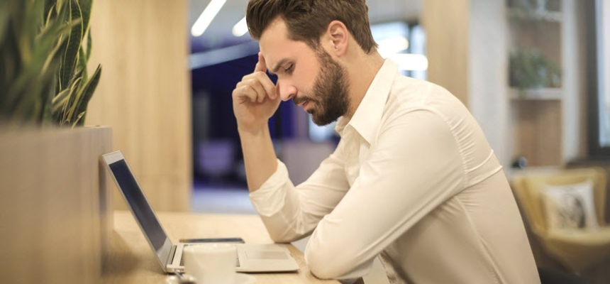 man looking at laptop thinking home price