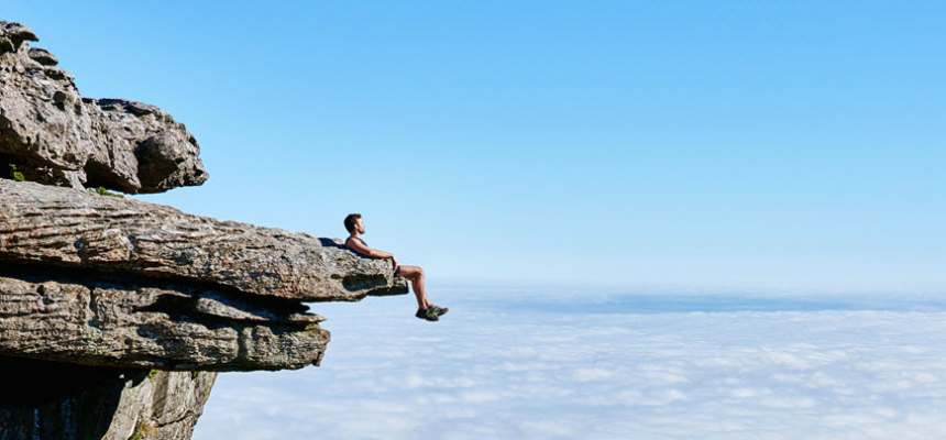 man cliff clouds overcome fear